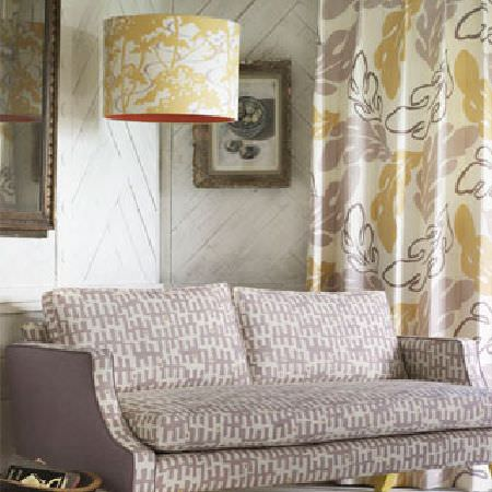 Rapture and Wright -  Rapture and Wright Collection - A grey and white patterned sofa, curtains with a large oak leaf print, a caramel and white light shade, and framed pictures