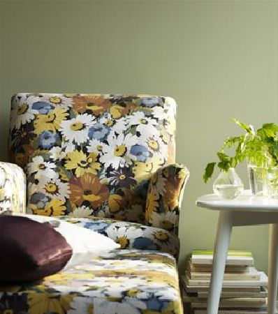 Sandberg -  Elin Fabric Collection - Armchair and footstool with a large white, gold and blue daisy print pattern, with a white wooden occasional table, glass vases, and cushion