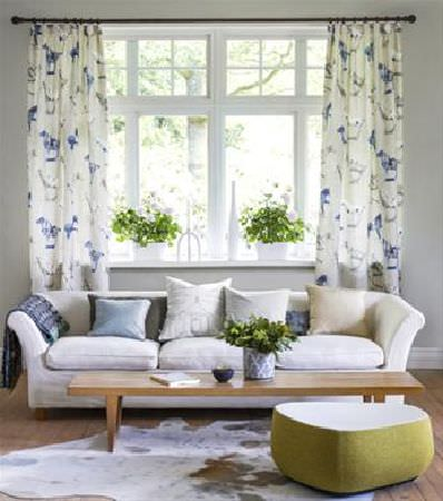 Sandberg -  Elin Fabric Collection - Cream, grey and blue horse print curtains, with a cream sofa, scatter cushions, wood coffee table, animal skin rug and triangular footstool