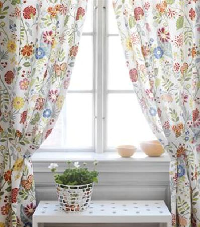 Sandberg -  Elin Fabric Collection - Variety of different flowers, in a range of colours, printed on white curtains and tiebacks, with a white table, flower pot and orange bowls