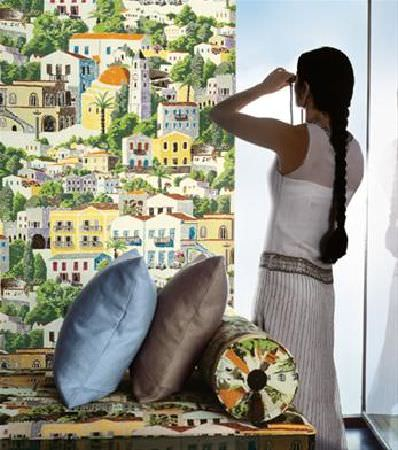 Sandberg -  Elin Fabric Collection - Fabric printed in a Mediterranean style building scene, covering a panel, chaise longue and bolster cushion, with cushions in blue and grey