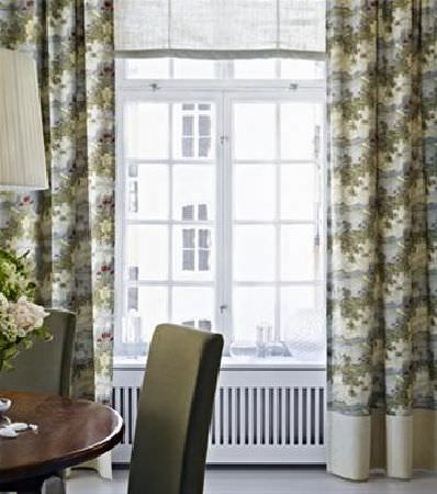 Sandberg -  Elin Fabric Collection - Pastel coloured patterned curtains with a cream strip at the bottom, with a round, polished wood table, olive green chairs, and a lamp