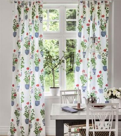 Sandberg -  Elin Fabric Collection - White curtains covered in a print of flowers and leaves in blue flowerpots, next to a white table, chairs with striped seats, and flower pots