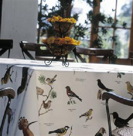 Sandberg -  Elin Fabric Collection - White tablecloth printed with different birds from around the world (and their names), with brown chairs and black tiered flower/fruit bowl