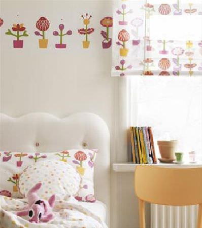 Sandberg -  Engla And Elliot Fabric Collection - Brightly coloured stylised flowers covering a pillowcase, blind and wallpaper banner, with peach coloured chair and round polka dot cushion