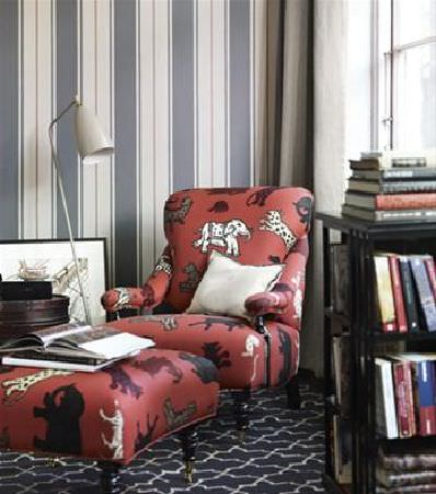 Sandberg -  Gotheborg Fabric Collection - Padded armchair and footstool covered in terracotta wild animal print fabric, beside a set of black shelves and a cream shaded floor lamp