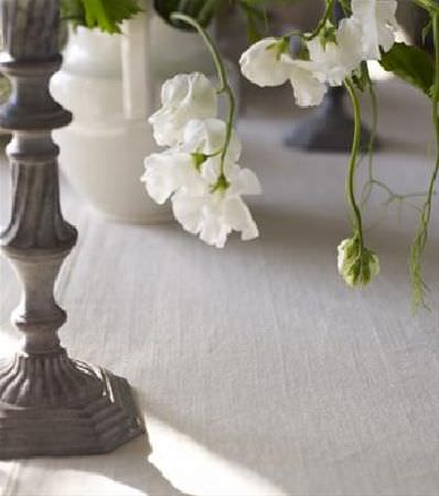 Sandberg -  Natur 2008 Book Fabric Collection - Beautifully carved grey stand to a stone effect flower pot, beside a large cream jug, on a plain cream tablecloth