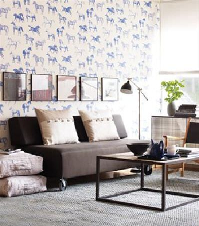Sandberg -  Nora Fabric Collection - Brown sofa on casters in front of blue and white horse print background, with a brown framed table, black floor lamp and four beige cushions