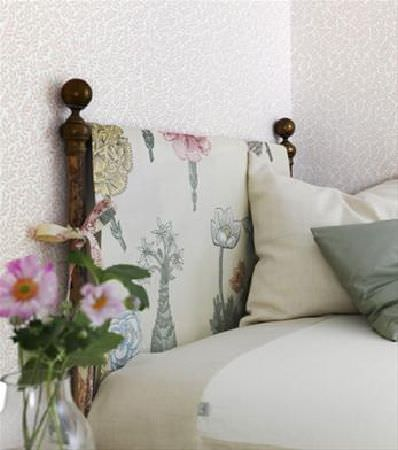 Sandberg -  Ofelia Fabric Collection - Wooden bed with fabric (cream, printed with large flowers) over the headboard, with cream sheet and cushion, green cushion, and glass vase