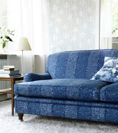 Sandberg -  Ofelia Fabric Collection - Sofa with stripes of dark and light blue intricately patterned fabric, with blue and white cushion, grey rug, wood side table and cream lamp