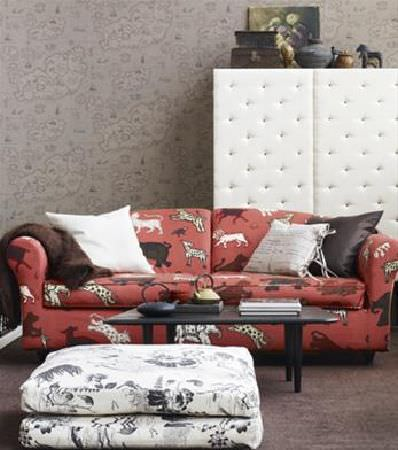Sandberg -  Ofelia Fabric Collection - Padded white cupboard, with terracotta coloured sofa covered in wild animal shapes, patterned monochrome footstool, and black coffee table