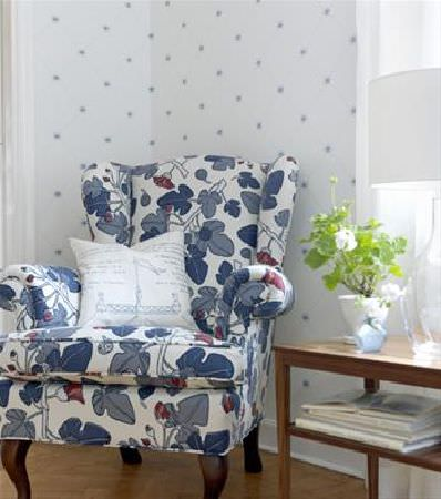 Sandberg -  Ofelia Fabric Collection - Sumptuous armchair in a fabric with large blue ivy leaves on a white background, beside a plain wood table, glass vase and white flower pot