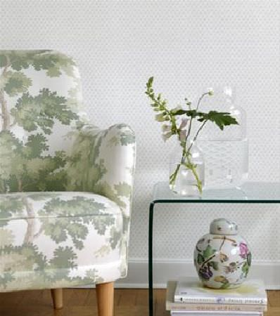 Sandberg -  Ofelia Fabric Collection - Design of tall trunks and leafy tree branches on a white armchair, a clear, moulded side table, two large glass jar vases, and a floral pot