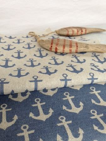 Sarah Hardaker -  Anchors Fabric Collection - Two small wooden fish atop two folds of anchor print fabric, one with a cream pattern on blue, and the other in the reverse colours