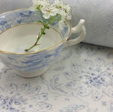Sarah Hardaker -  Antoinette Fabric Collection - Cream flowers placed in a pale blue, cream and gold patterned teacup, on matching floral and herringbone patterned fabrics