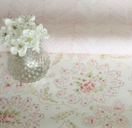 Sarah Hardaker -  Antoinette Fabric Collection - A fold of fabric with a pink and white herringbone design on green, pink and off-white floral fabric, with a glass vase