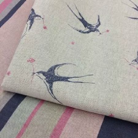 Sarah Hardaker -  Blakeney Fabric Collection - Elegant light grey fabric decorated with a pattern of blue swallows carrying a pink flower