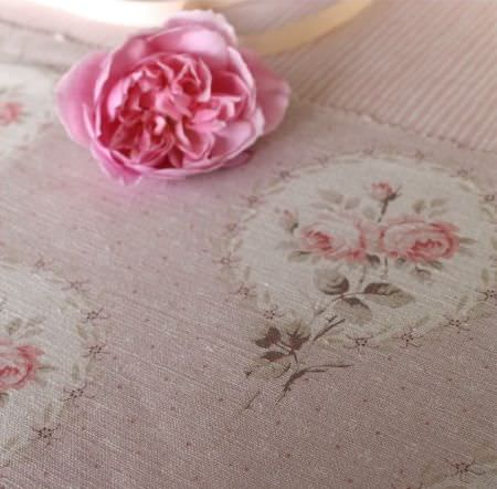 Sarah Hardaker -  Delfine Fabric Collection - A single pink flower lying on top of dusky pink, pale grey and off-white floral fabric and pinstripe patterned fabric