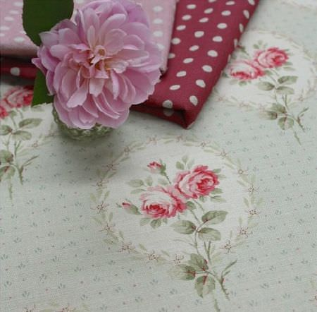 Sarah Hardaker -  Delfine Fabric Collection - Pale green, grey and red floral fabric beneath folds of polka dot fabric in red, pink and white, with a single pink flower