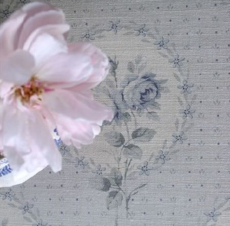 Sarah Hardaker -  Delfine Fabric Collection - A single pale pink flower above floral patterned fabric featuring a design in very light shades of grey and blue