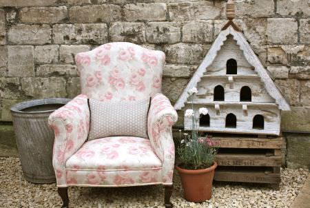 Sarah Hardaker -  Faded Roses Fabric Collection - Light pink and white floral padded armchair with a rectangular dotted cushion, beside a wooden pallet, triangular bird house and flower pots
