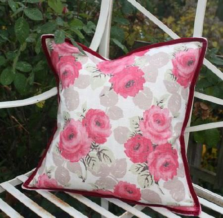 Sarah Hardaker -  Faded Roses Fabric Collection - Bright pink flowers with light brown leaves on a cream coloured cushion featuring a deep burgundy coloured trim, on a white metal bench