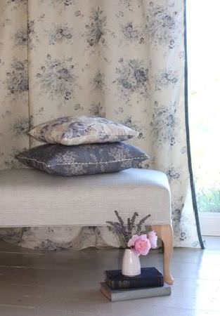 Sarah Hardaker -  Florence Fabric Collection - Plain light grey footstool with light wood legs, with blue and white floral fabric cushions and matching floor length curtains