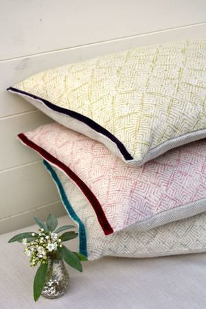 Sarah Hardaker -  Latika Fabric Collection - Stack of three cushions in cream, each with a subtle geometric print in either blue, green or pink, with a dark velour trim down the side