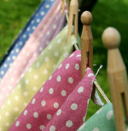 Sarah Hardaker -  Polka Dot Fabric Collection - Polka dot fabrics in seven different bright colours hanging from a washing line with vintage style wooden pegs
