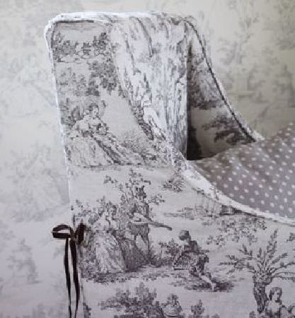 Sarah Hardaker -  Pompadour Toile Fabric Collection - An armchair in off-white fabric featuring large, shaded grey scenes including people, with a black ribbon tie and a grey polka dot cushion