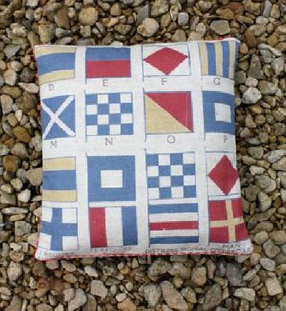 Sarah Hardaker -  Semaphore Fabric Collection - A square white scatter cushion printed with neat rows of blue, red and yellow-gold semaphore flags