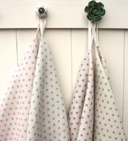 Sarah Hardaker -  Spotty Fabric Collection - A round coat hook and a flower shaped coat hook, each with two fabrics hanging from it in cream, with different pastel coloured polka dots