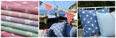 Sarah Hardaker -  Stars Fabric Collection - Stack of multicoloured star print fabrics, with blue and white star print cushions, a blue and white polka dot cushion and patterned bunting