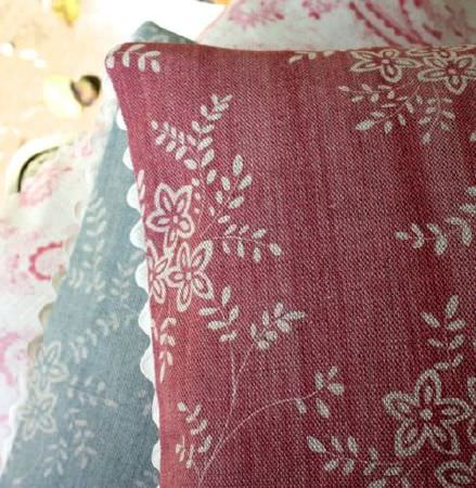 Sarah Hardaker -  Suzi Fabric Collection - Distressed red and light blue cushions, both featuring a subtle, simple light grey floral pattern and a trim which is scalloped and white