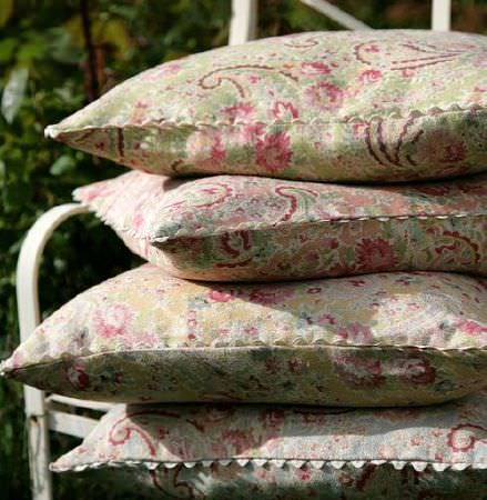 Sarah Hardaker -  Vintage Paisley Fabric Collection - A stack of four busily patterned cushions featuring florals and paisley shapes, mainly in green, pink, yellow, white and blue shades