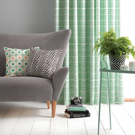 Sian Elin -  Sian Elin Fabric Collection - Mint green curtain with soft tribal pattern and plain grey armchair covered with modern cushions