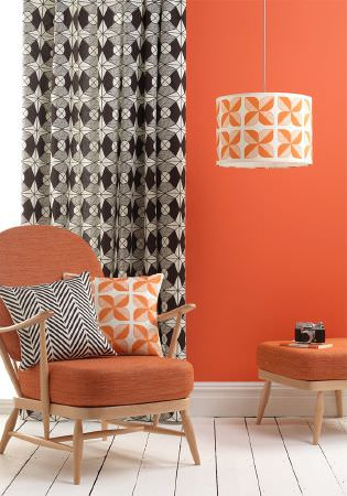 Sian Elin -  Sian Elin Fabric Collection - Black and white geometric pattern on a curtain, plain orange chair and a white cushion with interesting orange flowers