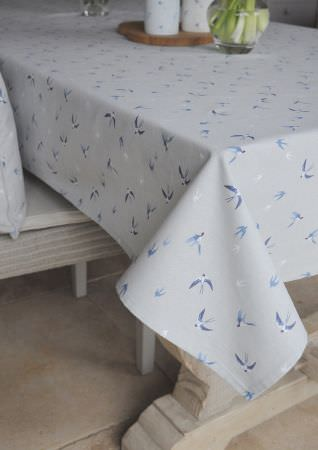 Sophie Allport -  Sophie Allport Fabric Collection - Pale grey tablecloth scattered with blue and white swallows in flight, with a matching cushion on a grey striped chair, with a glass vase