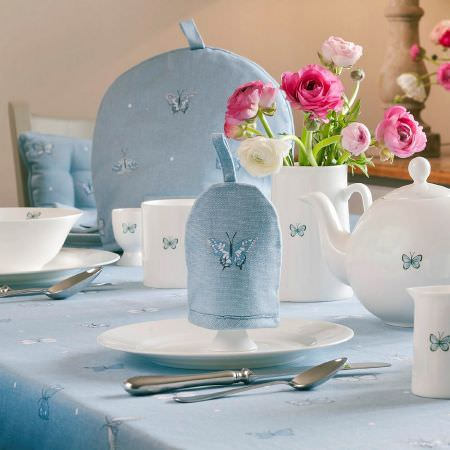 Sophie Allport -  Sophie Allport Fabric Collection - Small blue butterflies printed ona white tea set including teapot, bowl, milk jug and eggcup and on a blue tablecloth, egg cosy and teapot cosy