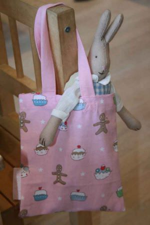 Sophie Allport -  Sophie Allport Fabric Collection - Pink fabric bag printed with cupcakes and gingerbread men, hanging over the back of a wooden chair and holding a stuffed rabbit toy