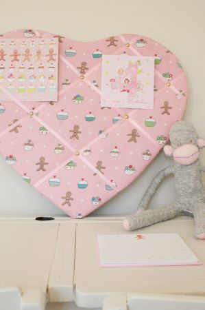 Sophie Allport -  Sophie Allport Fabric Collection - Heart shaped pin board with a pink, white, blue, green and brown cupcake and gingerbread man print, above a white desk with a toy monkey
