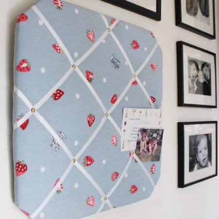 Sophie Allport -  Sophie Allport Fabric Collection - Black and white picture frames beside a square pinboard with the edges cut off, which is covered in a blue, red and white strawberry print