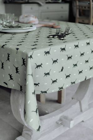 Sophie Allport -  Sophie Allport Fabric Collection - A green tablecloth patterned with rows of black cats on a solid white wood table, with white crockery, silver cutlery and a wood bread board