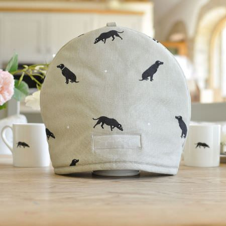 Sophie Allport -  Sophie Allport Fabric Collection - Black silhouettes of sitting and sniffing dogs printed with tiny white dots on a light grey teapot cover, withblack and white dog print mugs