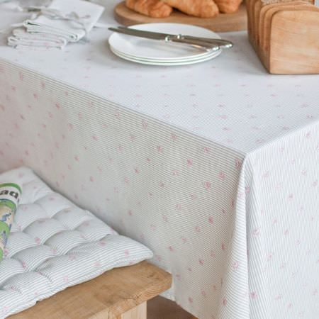 Sophie Allport -  Sophie Allport Fabric Collection - Tiny pink flowers on a light blue and white striped tablecloth and quilted seat cushion, with a wooden seat, white napkins, plates and cutlery