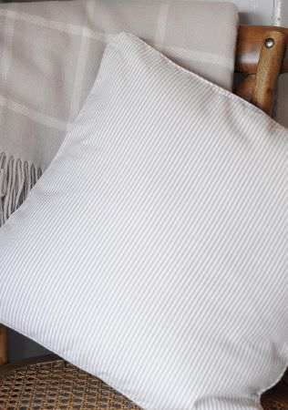 Sophie Allport -  Sophie Allport Fabric Collection - A very subtly striped light grey and white scatter cushionwith a grey and white checked, fringed blanketon a woven wicker and wood chair