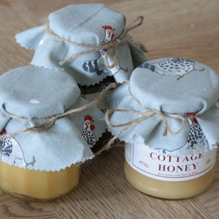 Sophie Allport -  Sophie Allport Fabric Collection - Jars of honey with the lids covered inlight grey fabric with a pattern of chickens and tiny eggs, which has been secured with brown twine