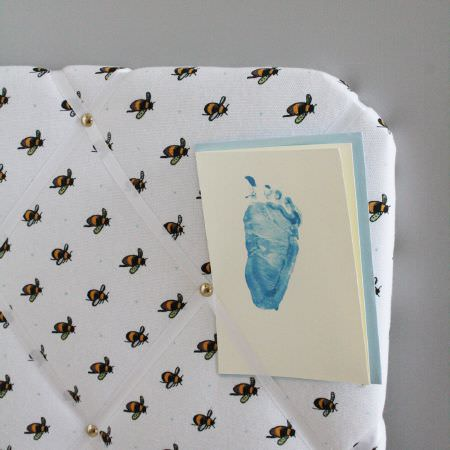 Sophie Allport -  Sophie Allport Fabric Collection - A pinboard covered in white fabric with a pattern of rows of bees and secured with diagonal rows of plain white ribbon
