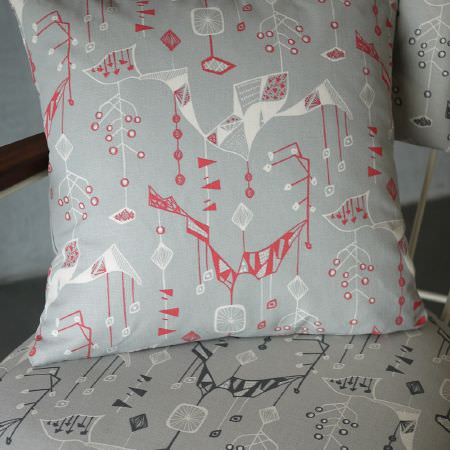 St Judes -  Alice Stevenson Fabric Collection - Random abstract geometric patterned fabric, in a grey, white and salmon coloured cushion, and a grey, white and dark teal chair