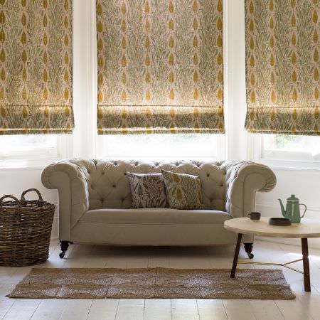 St Judes -  Angie Lewin Fabric Collection - High-backed cream padded sofa, with patterned blinds in cream, gold and grey, with a brown rug, large woven basket and round wood table